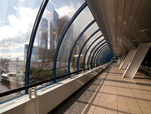 Modern covered footbridge. Covered bridge and skyscrapers beyond window. Moscow City royalty free stock image
