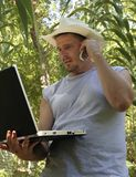Computer in a Cornfield. Farmer telecommutes from his farm in the Southern part of the United States, out in the cornfield with a laptop and mobile phone