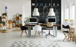 Modern coworking space. Black and white, modern coworking space with blackboard, desk, computer stock images