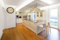 Modern cream kitchen. Modern beautiful kitchen and parquet in design house royalty free stock image