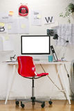 Modern creative workspace with computer and red chair. Royalty Free Stock Photo