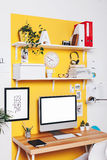 Modern creative workspace on yellow wall. Stock Photos