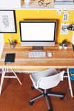Modern creative workspace on yellow wall. Royalty Free Stock Photos