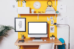 Modern creative workspace on yellow wall. Royalty Free Stock Photography