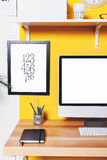 Modern creative workspace on yellow wall. Stock Photo