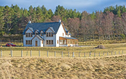 Modern Croft house. An image of a modern Croft house in the Scottish countryside surrounded by fields and forest with chimnies, porch  and sun-room Royalty Free Stock Photography