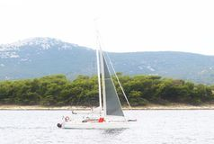 A modern cruise sailing yacht with a Bermuda sloop-type rig goes past the green coast of the Croatian Riviera on a sunny summer. Day. Adriatic Sea of the royalty free stock images