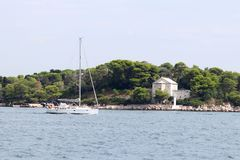 A modern cruise sailing yacht with a Bermuda sloop-type rig goes past the green coast of the Croatian Riviera on a sunny summer. Day. Adriatic Sea of the stock photo