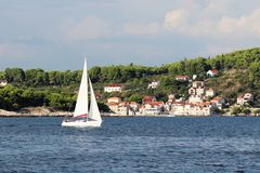 A modern cruise sailing yacht with a Bermuda sloop-type rig goes past the green coast of the Croatian Riviera on a sunny summer. Day. Adriatic Sea of the stock photos