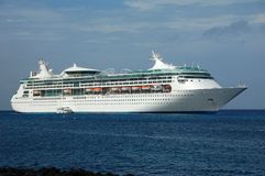 Modern cruise ship in the Caribbean. Cruise ship moored at sea with a passenger tender boat nearby Stock Photos