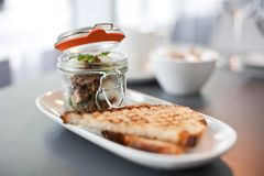 Modern cuisine breakfast served in a small preserving jar. With triangles of soudough toast Stock Images