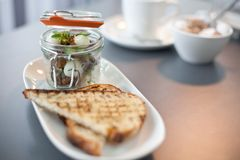 Modern cuisine breakfast served in a small preserving jar. With triangles of soudough toast Royalty Free Stock Photography