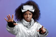 Modern curly brown-haired girl dressed in a silver-colored jacket wearing on her head the virtual reality glasses poses royalty free stock images