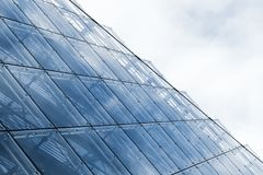 Blue curtain wall made of glass and steel. Modern curtain wall made of glass and steel under blue sky Stock Images