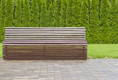 Modern curve shaped brown wooden bench outdoor furniture in the park as background image Stock Photos