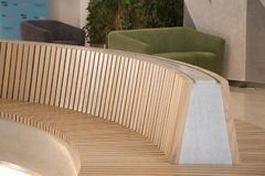 Modern curved shaped brown wooden bench indoor stock image
