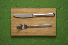 Modern Cutlery set on green fabric background Stock Photo