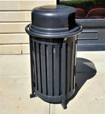 Modern cylindrical black trash receptacle. Black metal cylindrical modern trash receptacle, outdoors in sunny shopping area Royalty Free Stock Photography