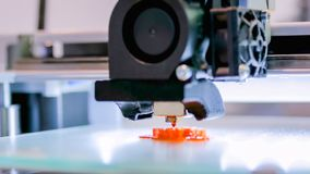 Modern 3D printer machine printing plastic model. Print head of 3D printer machine printing plastic model at modern scifi technology exhibition. 3D printing stock images