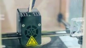 Modern 3D printer machine printing plastic model. Print head of 3D printer machine printing plastic model at modern scifi technology exhibition. 3D printing royalty free stock photo
