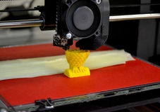 Modern 3D printer printing figure close-up. Automatic three dimensional 3d printer performs plastic yellow colors modeling in laboratory. Progressive modern stock photo