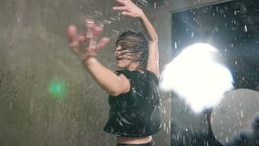Modern dance wet young woman in the rain on stage. Wet dancer girl dancer circling around herself in the studio under. The rain water, slow motion stock footage