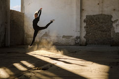 Modern dancer jumping high in the air in abandoned building Stock Image