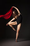 Modern dancer with red fabric posing on grey Stock Image