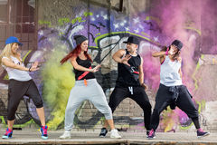 Modern dancing group exercises body jam outside. Young modern dancing group practice body jam in front colorful wall Stock Photography