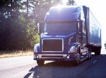 Modern dark big rig blue semi truck with trailer on the road in. Popular model of modern dark blue big rig semi truck with dry van trailer transport cargo on the stock photos