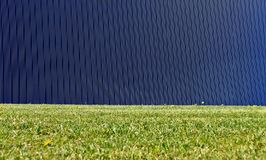 Modern dark blue aluminium cladding wall with vertical stripes and a meadow in front. Background for copy space.  stock image