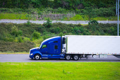 Modern dark blue semi truck reefer trailer profile on green road Royalty Free Stock Photos