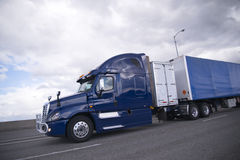 Modern dark blue semi truck with trailer and storage unit Royalty Free Stock Photo