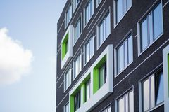 Modern dark brown building in Wageningen with big windows and the blue sky in the background. New and modern building in Wageningen with big windows and the blue royalty free stock photo