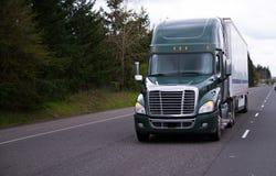 Modern dark green semi truck and trailer on straight road Royalty Free Stock Photo