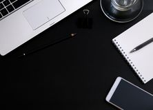 Modern dark office Desk. Computer, mobile phone,Notepad, pen and Cup. The view from the top Royalty Free Stock Photos