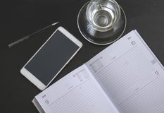 Modern dark office Desk. Computer, mobile phone,Notepad, pen and Cup. The view from the top Royalty Free Stock Image