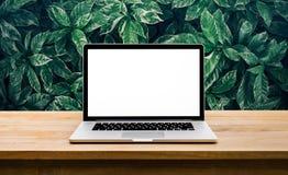 Modern dator, bärbar dator med den tomma skärmen på tabellen med det gröna bladet Arkivbild