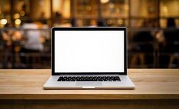 Modern dator, bärbar dator med den tomma skärmen på tabellen med suddighetskafét Arkivfoton