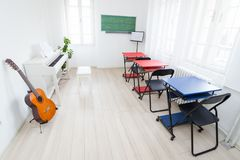 Modern daylight classroom for teaching music. Guitar, white piano and greenboard in music classroom. Modern daylight classroom for teaching music. Guitar, white royalty free stock image