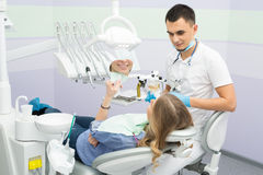 Modern dental clinic, young dentist working Stock Photos