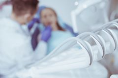 Modern dental equipment placing in office. Working tools. Selective focus of sophisticated dental instruments while dentist examining patient on the background stock image