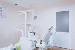 Modern dental room. Dentists chair and tools. Dental care, dental hygiene, checkup and therapy concept. White tone. Modern dental room. Dentists chair and tools royalty free stock images