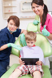 Modern dental team offering entertainment for kid patient Stock Image