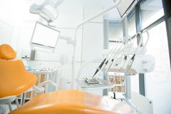 Modern dentistry clinics. Yellow leather armchair for clients of modern dentistry clinics with set of drills and instruments near by Stock Photography