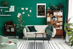 Modern design botanic living room. Modern design, botanic living room interior with cozy, beige sofa, antique furniture, home library, and teal green wall stock photo