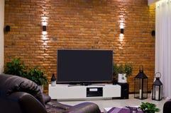 Modern design för hem- rum med väggen för röd tegelsten och framlänges ledd television arkivbild
