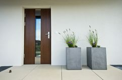 Two cubic concrete flower pots at front door of a house royalty free stock photo