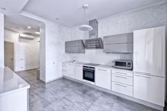 Interior design modern kitchen in the new house. Modern design interior with white glossy kitchen in a luxurious apartment in gray and white tones Royalty Free Stock Image