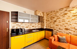 Orange room kitchen. Modern design of an orange and yellow theme room with corner mounted kitchen and sandstone tiled wall Stock Photos